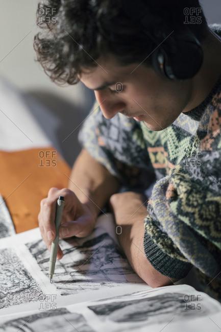 Male artist drawing in sketchbook in artists studio