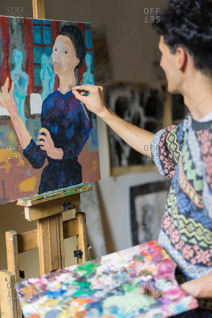 Male artist painting canvas on easel in artists studio