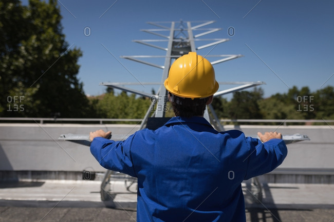 Rear view of male worker using machine at solar station