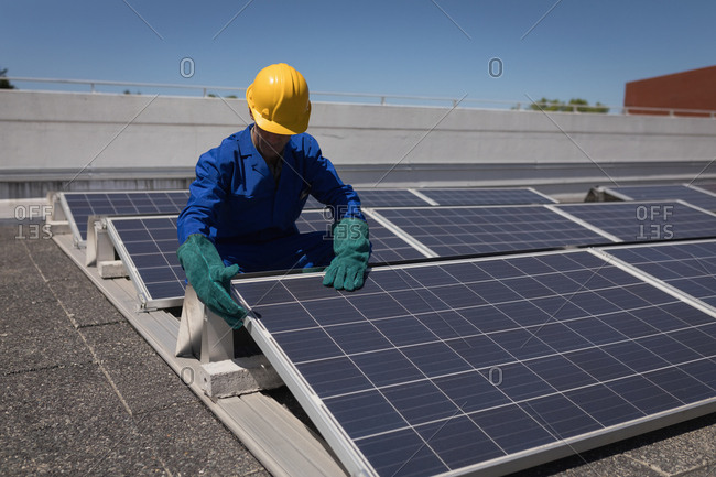 Male worker working at solar station on a sunny day
