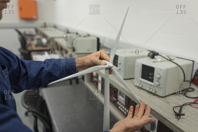 Male worker working on windmill in office