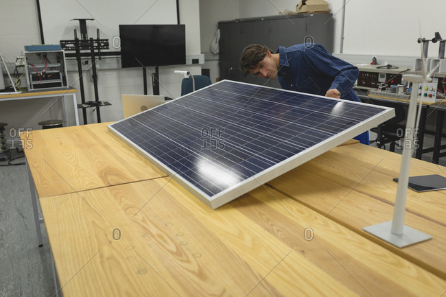 Male worker working on solar panel in office