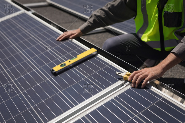 Mid section of male worker working on solar panels at solar station