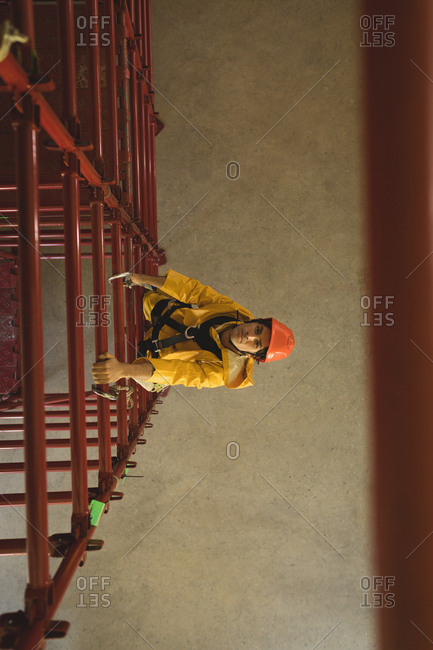 Young male worker climbing scaffolding at solar station