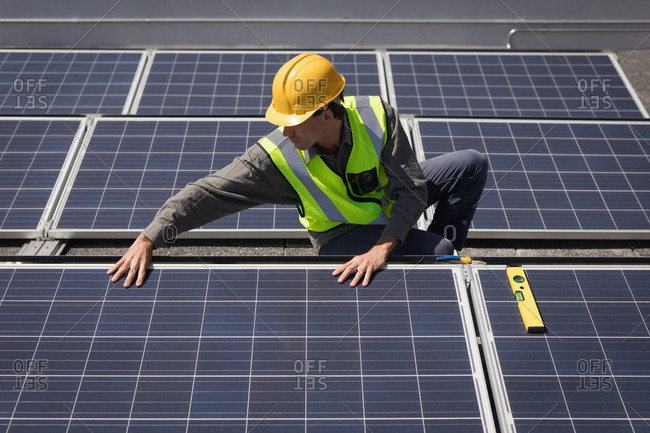 Male worker working on solar panels at solar station on a sunny day
