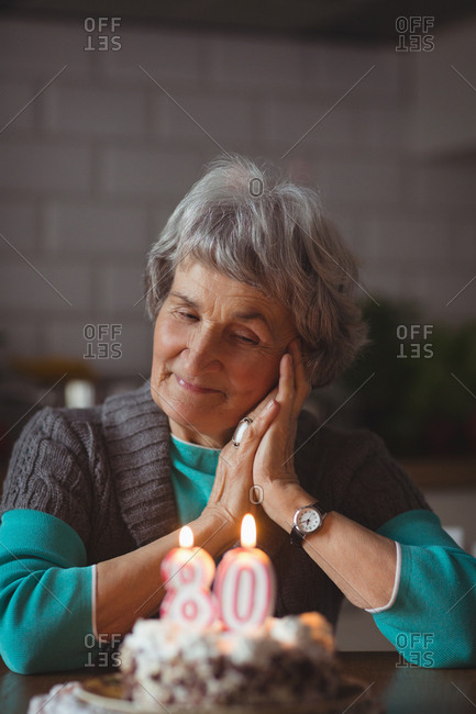 Thoughtful senior woman with birthday cake at home