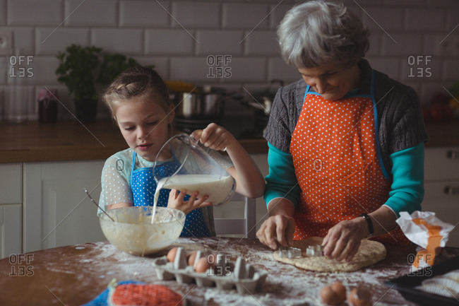 Grandmother and granddaughter preparing cookies in kitchen at home