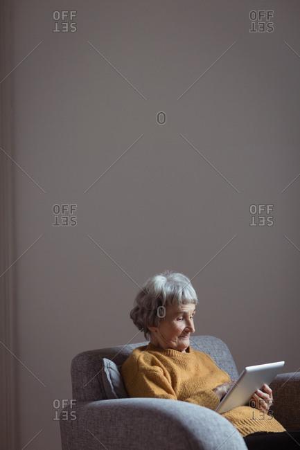Senior woman using digital tablet in living room at home