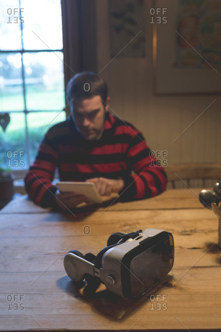 Virtual reality headset on table while man using digital tablet at home