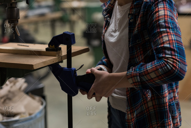 Mid section of female carpenter using screw clamp on a piece of wood at workshop