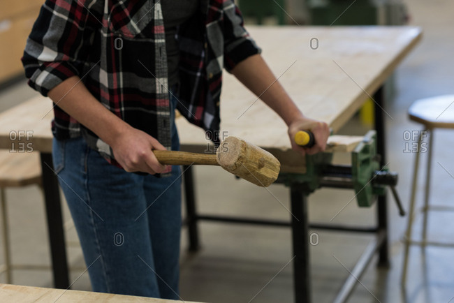 Mid section of female carpenter using chisel with hammer on a piece of wood at workshop