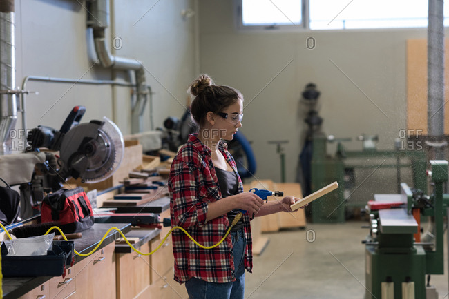 Female Carpenter Using A Machine On A Piece Of Wood At Workshop
