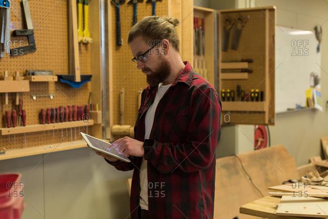 Male carpenter using digital tablet at workshop