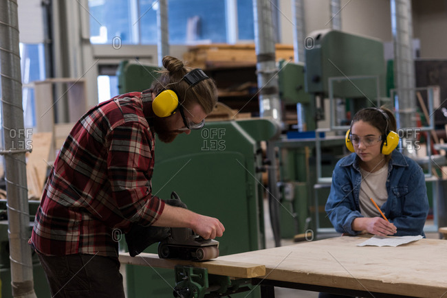 Male carpenter using jack plane while female looking at him in workshop