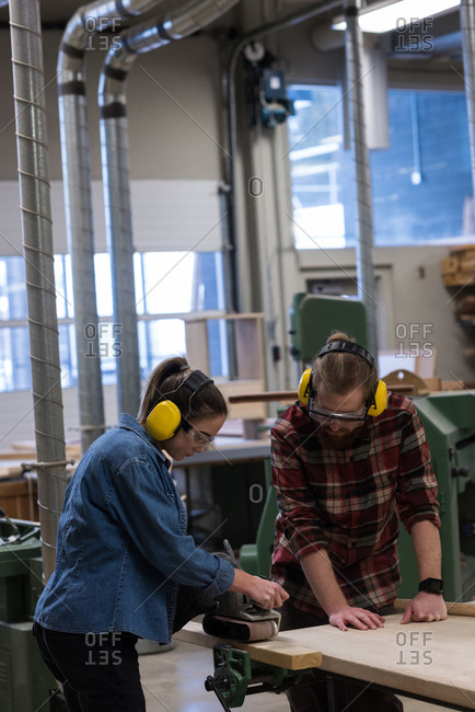 Female carpenter using jack plane while male looking at her in workshop