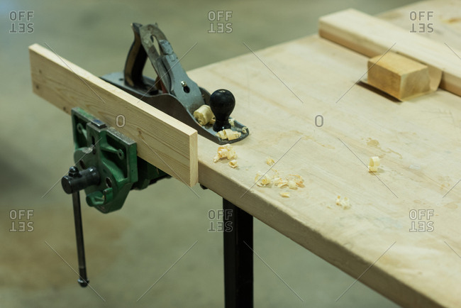 Jack plane with piece of wood on a table at workshop