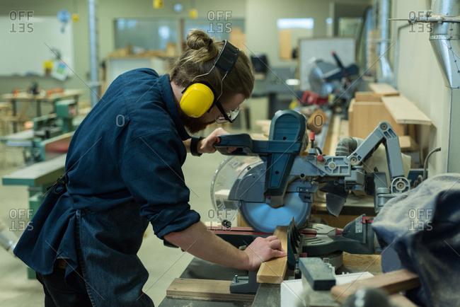 Male carpenter using grinder cutting machine at workshop