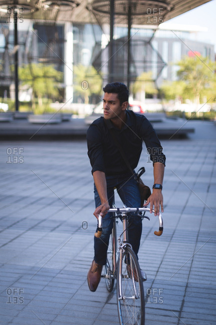 Young businessman riding a bicycle in office premises