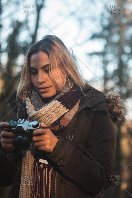 Young woman reviewing pictures on digital camera