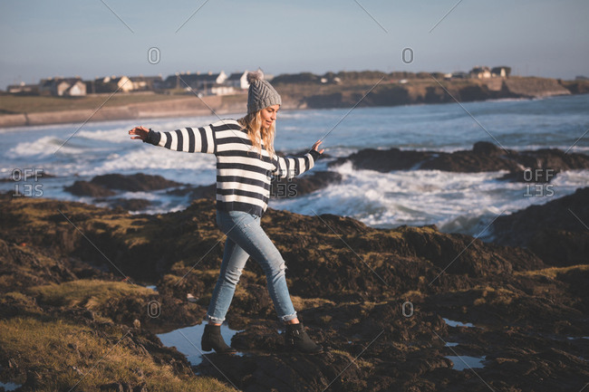 Woman walking with arms outstretched at beach on a sunny day