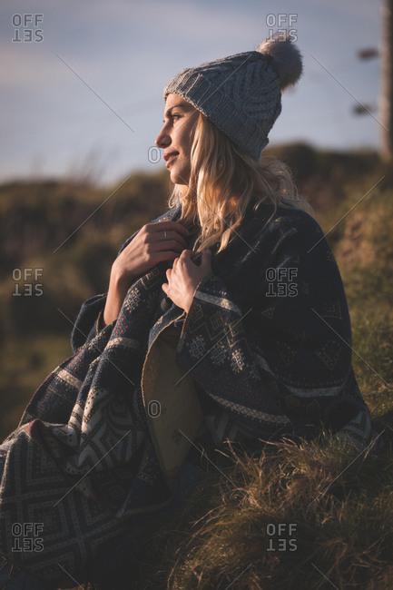 Thoughtful woman in shawl relaxing near beach