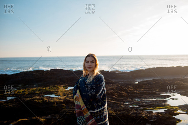 Portrait of woman in shawl standing on a beach