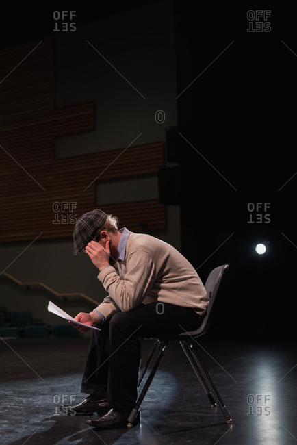 Male actor reading script on stage at theatre