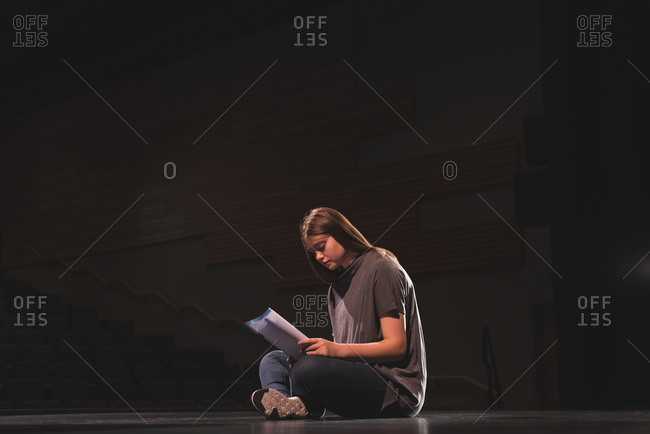 Female actress reading script on stage at theatre
