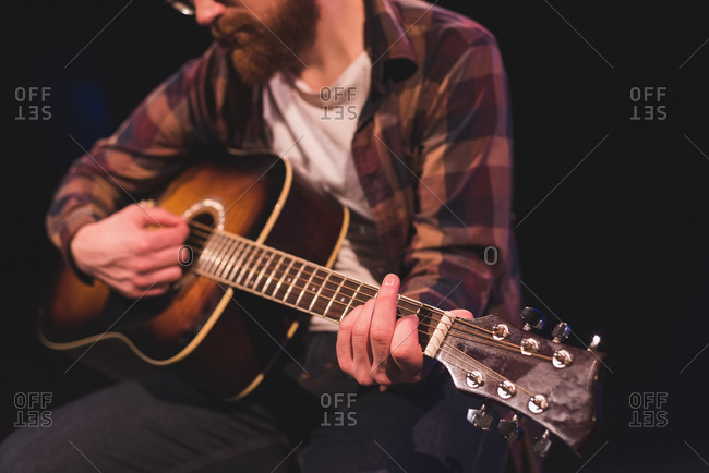 Man playing guitar on stage at theatre