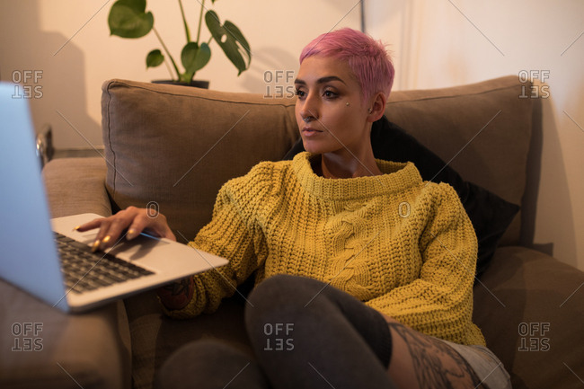 Stylish woman using laptop in living room at home