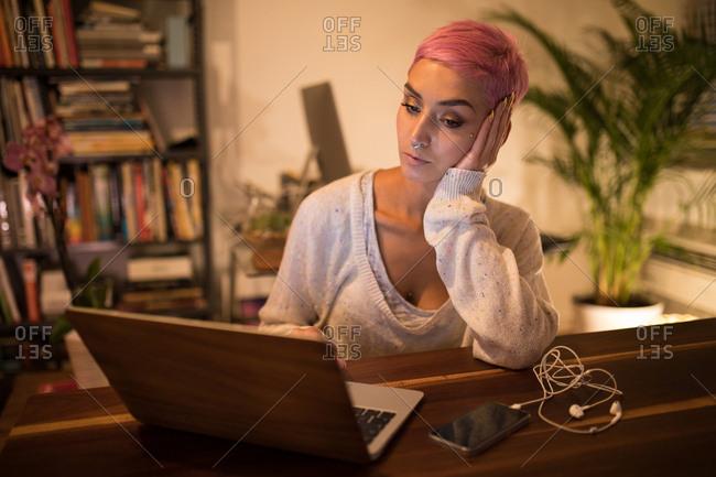 Stylish woman using laptop at home