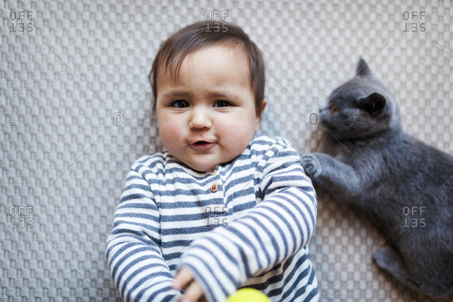 Baby making funny faces lying down with cat