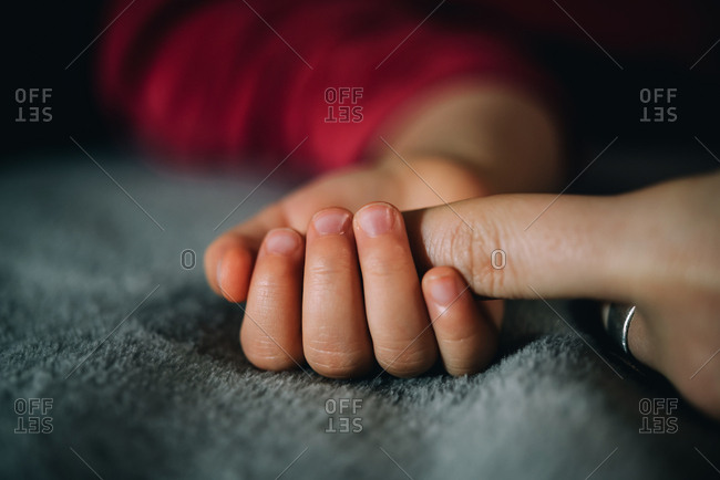 Toddler's small hand holding mother's finger on a soft blanket