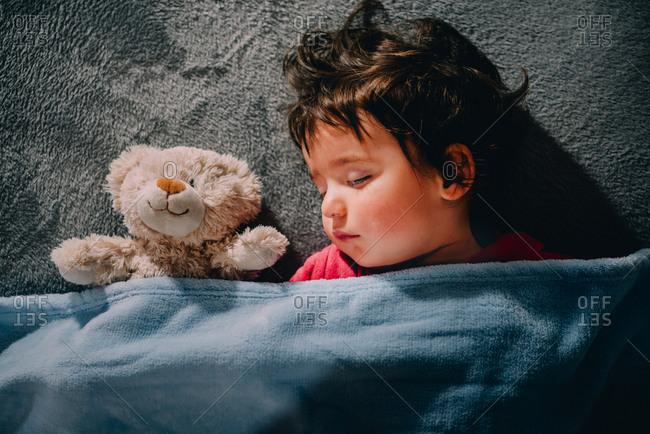 Girl sleeping peacefully with teddy bear under blanket
