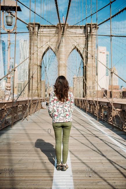 New York City - September 11, 2017: Female tourist standing still in middle of Brooklyn Bridge