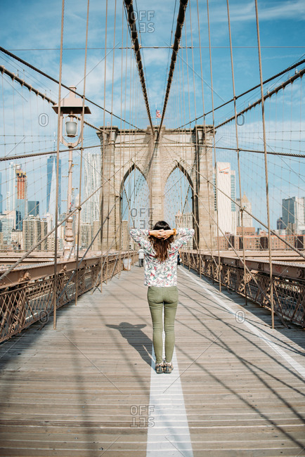 New York City - September 11, 2017: Woman standing on Brooklyn Bridge enjoying view of Manhattan