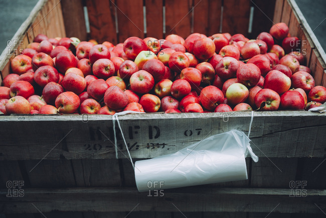 Fresh red apples in wooden crate at market