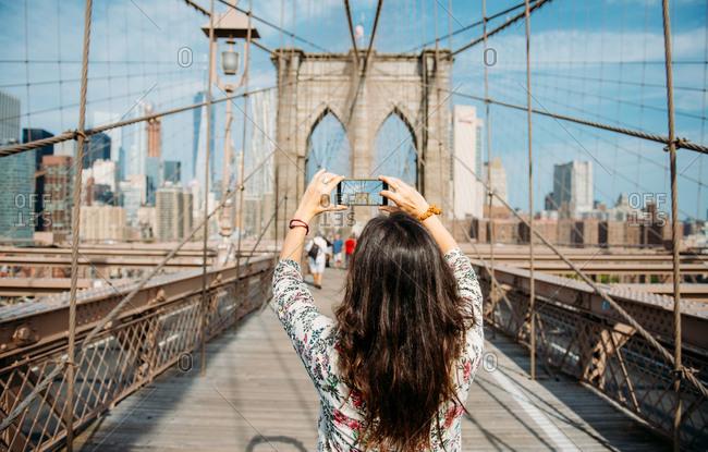 Woman standing on Brooklyn Bridge enjoying view of Tourist capturing detail of Brooklyn bridge on smartphone