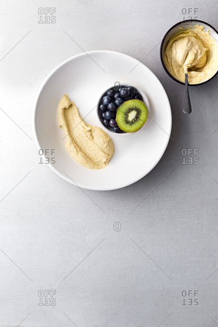 Hummus, blueberries and kiwi on dinner plate