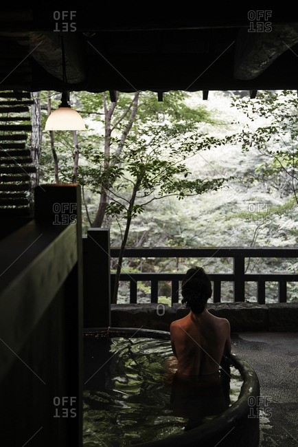 Woman soaking in private hot spring bath with a view of the forest in Kyushu, Japan