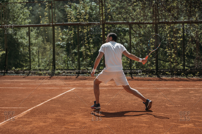 Young tennis player ready for serve on outdoors court