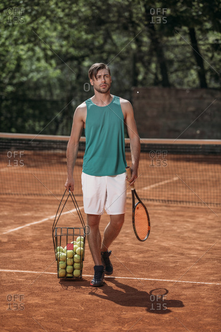 Tennis player carrying basket of balls on court