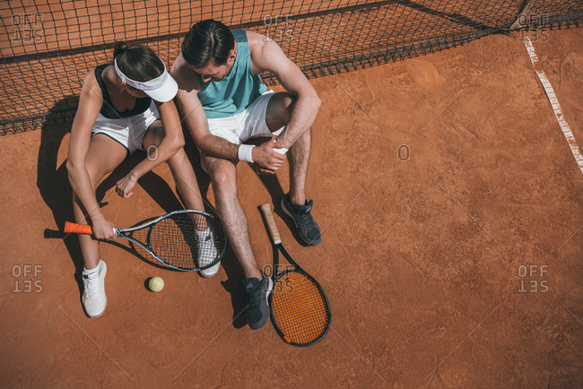 High angle view of young couple leaning back on net and relaxing on tennis court