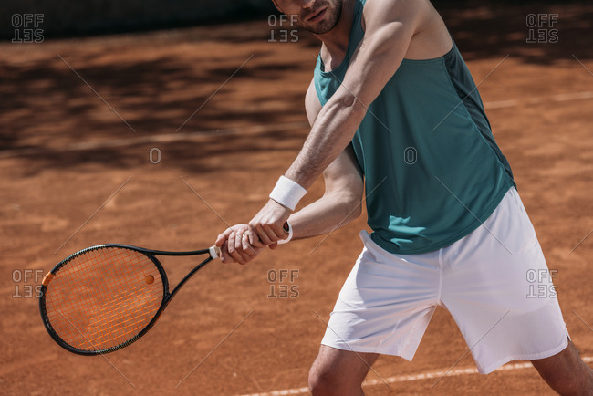 Cropped shot of tennis player making hit with racket