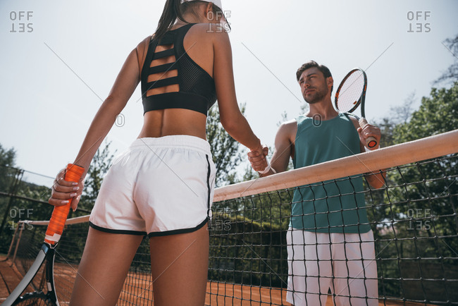 Young man and woman shaking hands before tennis match