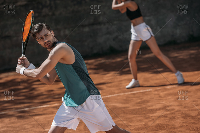 Young athletic couple playing tennis as team