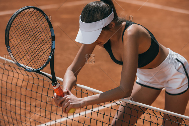 Sportive woman leaning on tennis net and resting after match