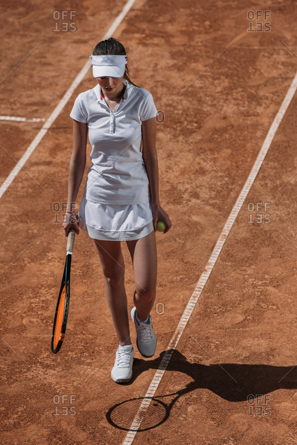Young sportive woman with racket and tennis ball walking by court
