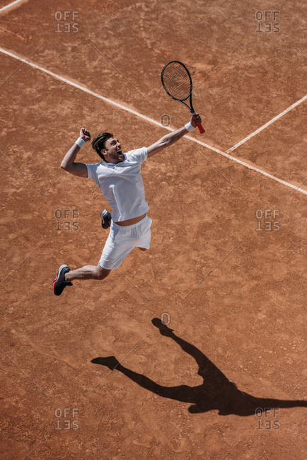 High angle view of athletic tennis player making hit in jump