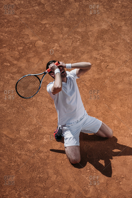 High angle view of man standing on knees and crying after he lose tennis match
